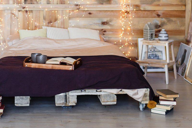 Schlafzimmer mit Euro-Paletten und Lichterketten
