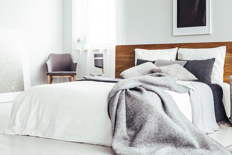Bett mit weißen und grauen Accessoires